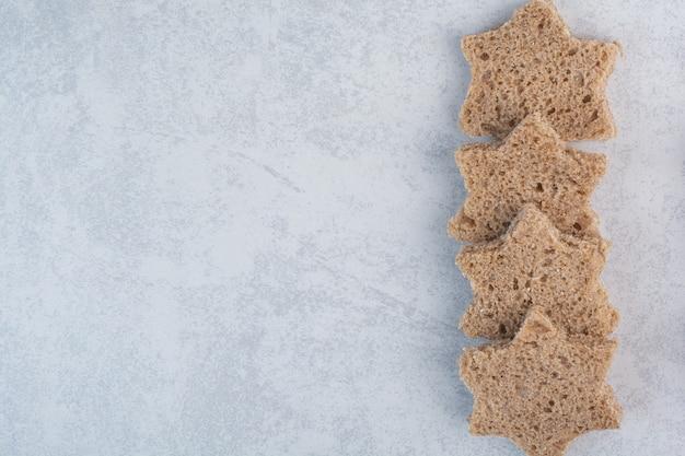 Ломтики черного хлеба в форме звезды на каменной поверхности