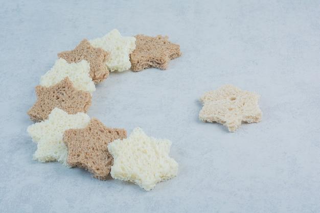 Fette di pane bianco e nero a forma di stella su fondo di marmo. foto di alta qualità