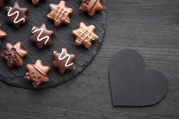 Star-shaped chocolates on dark textured background with heart