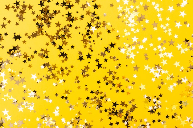 Star shaped confetti yellow background