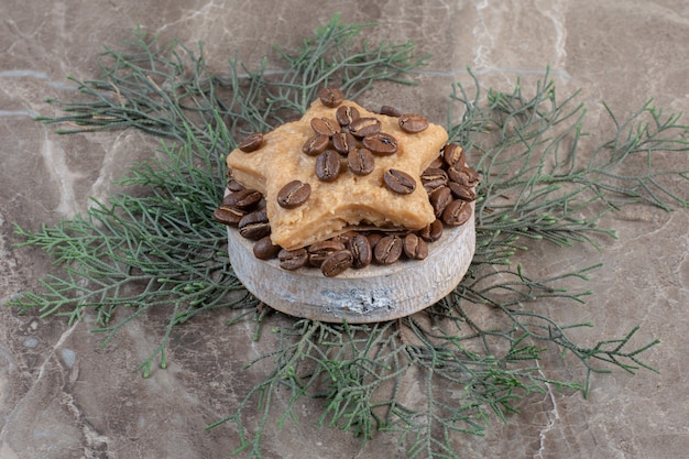 Biscotto a forma di stella su un mucchio di chicchi di caffè su un piccolo piedistallo su marmo.