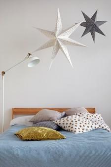 아늑한 침실에 베개가있는 편안한 침대와 현대적인 램프 위에 매달려있는 별 모양의 장식
