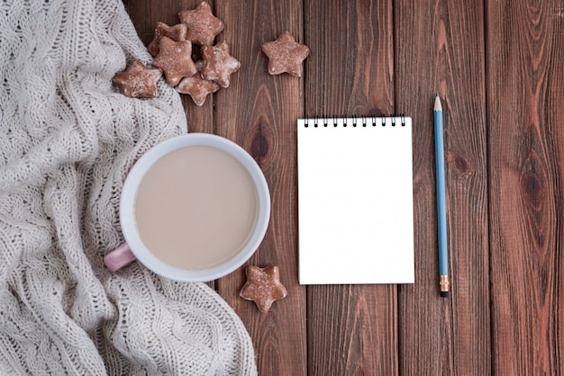 Star shaped ginger cookies and cup of coffee with empty notebook.