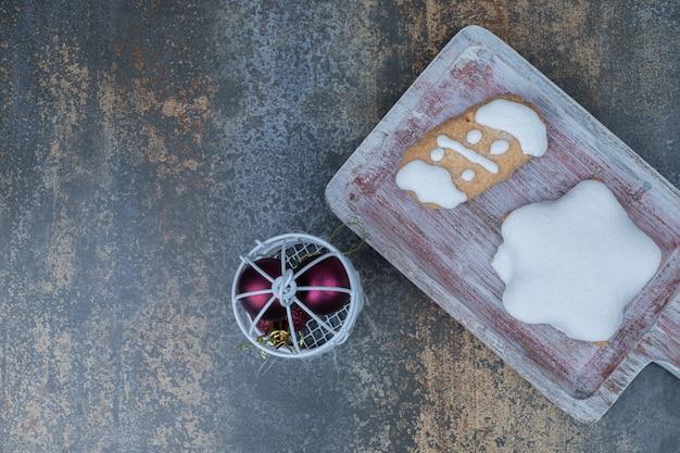 Biscotti di panpepato a forma di stella e mazzo di palline sulla superficie di marmo. foto di alta qualità