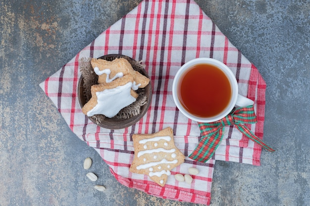 Star shaped gingerbread cookies and cup of tea on tablecloth. high quality photo
