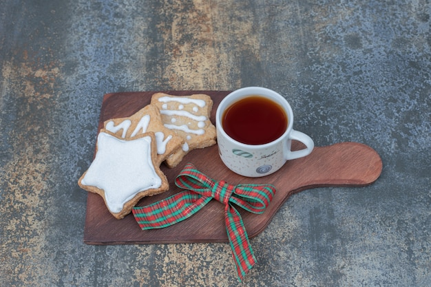 Star shaped gingerbread cookies and cup of tea on wooden board. high quality photo