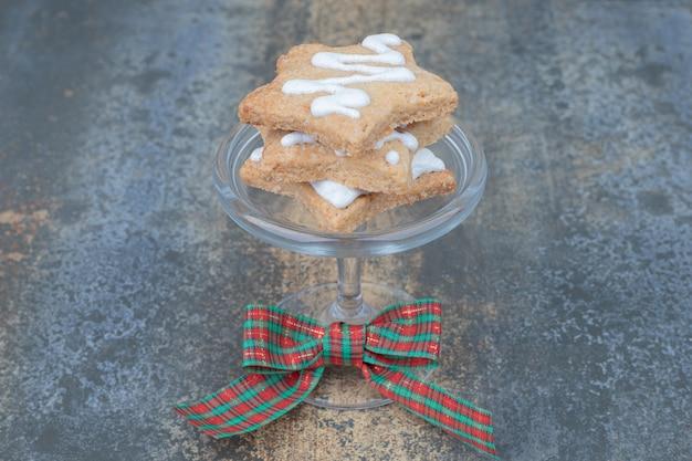 리본으로 장식 된 유리에 별 모양의 진저 쿠키. 고품질 사진