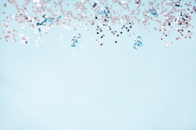 Star shaped silver sequins and silver ribbons on blue background. copy space.
