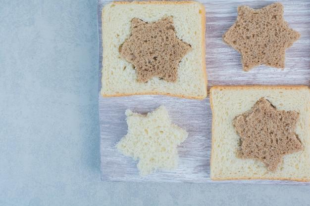 Fette di pane bianco e nero a forma di stella e quadrata su fondo di marmo. foto di alta qualità