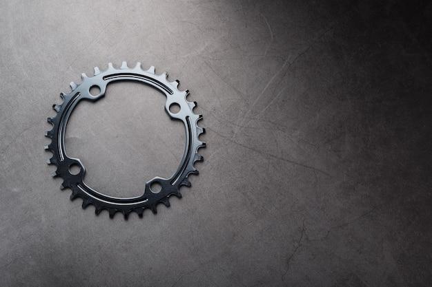 黒い表面に自転車のチェーン機構を備えた星の歯のパターン。ダークキー、ナローワイドバイク用の上面図ブラックスターコネクティングロッドシステム。