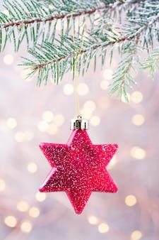 Звездная игрушка висит на елке.