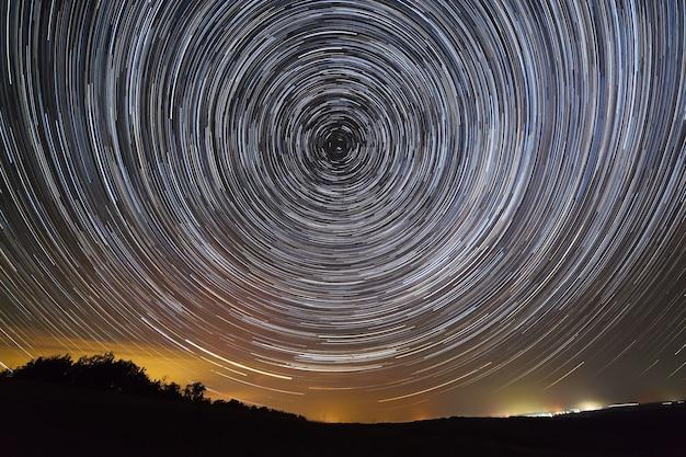 Звездные следы в ночном небе. вид на звездное пространство и свет над горизонтом.