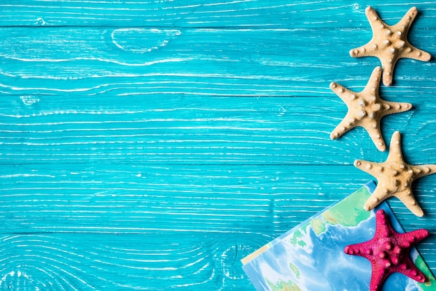 Starfish and map located on blue wooden background
