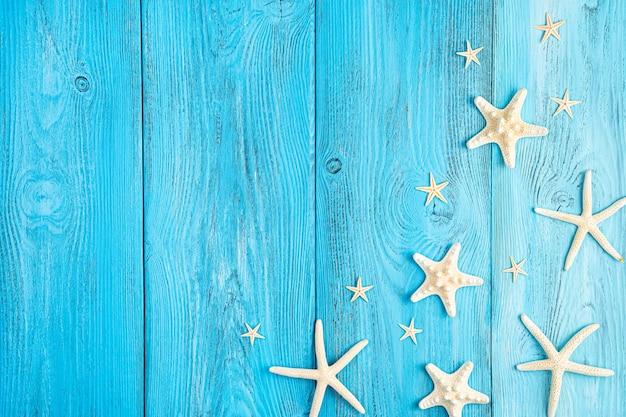 Морские звезды разной формы на синем фоне. летний фон. скопируйте пространство.