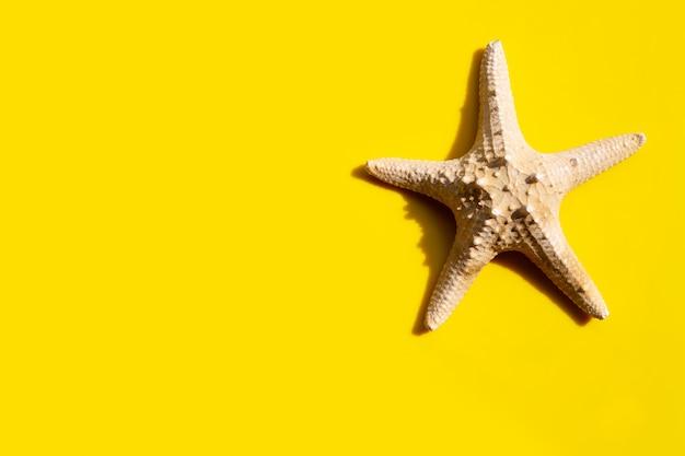 Морская звезда на желтом. наслаждайтесь концепцией летнего отдыха.