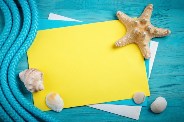 Starfish, pebbles and shells lying on a blue wooden surface with postcard