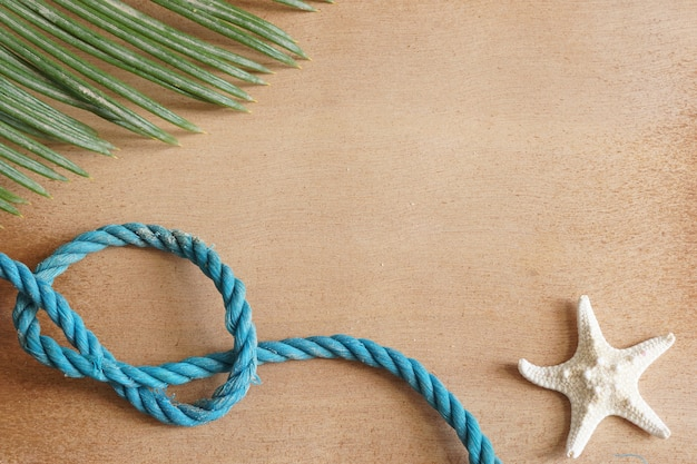 Starfish, rope and palm leaf on a wooden surface, copy space for text.