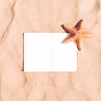 Starfish on sand background with blank notebook