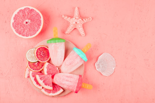 Starfish and scallop shell with grapefruit slices and popsicles on coral textured background