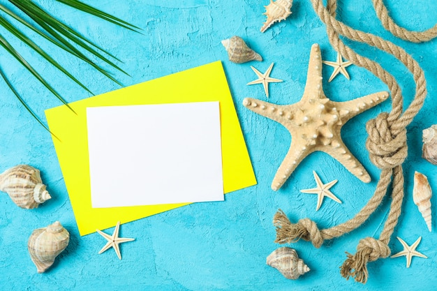 Starfish, seashells, sea ã¢â€â‹ã¢â€â‹rope, palm leaf  and space for text on two tone background, top view. summer vacation concept