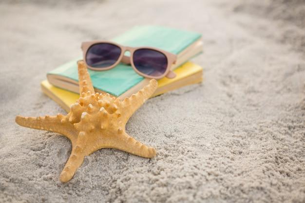 Starfish, sunglasses and books on sand