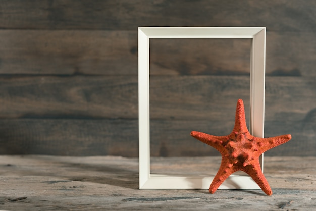 Starfish and white picture frame on old wooden background