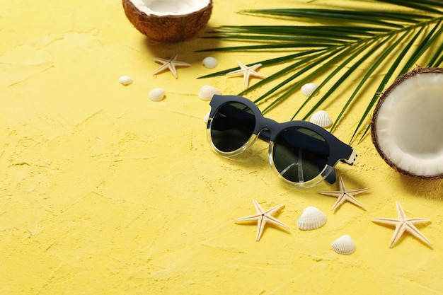 Starfishes, coconut, palm branch and sunglasses on yellow, space for text