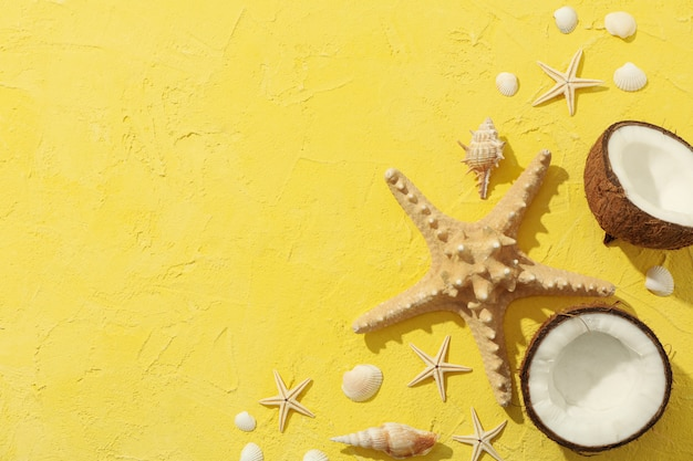 Starfishes, coconut and seashells on yellow surface