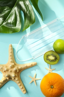 Starfishes, fruits, palm leaf and mask on blue isolated background