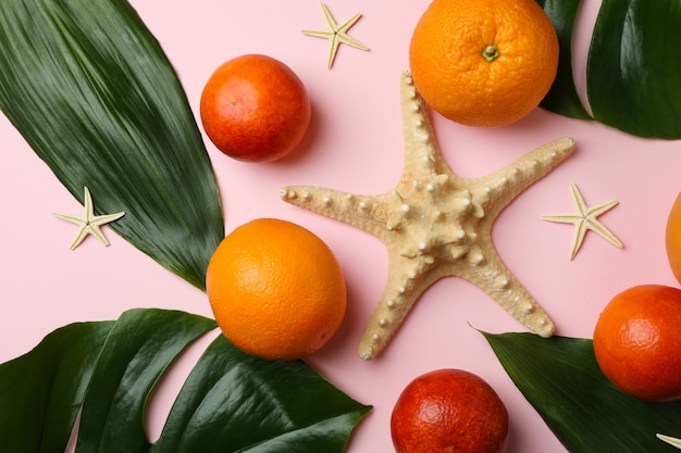 Starfishes, fruits and palm leaves on pink isolated background