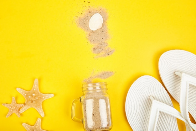 Starfishes and seashells, white flip flops, glass with sand on yellow background top view