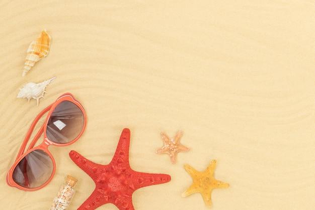 ヒトデ、サングラス、砂の上の貝殻