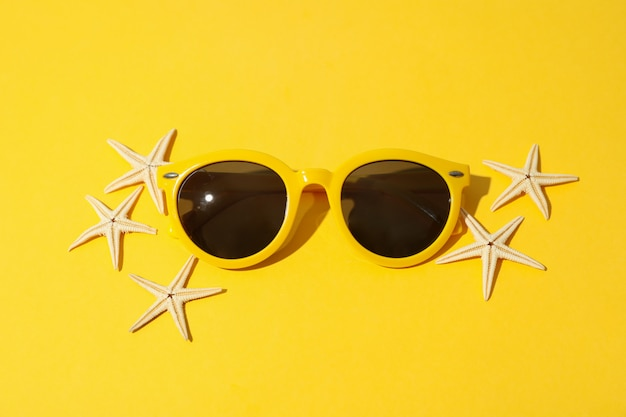 Starfishes and sunglasses on yellow, top view