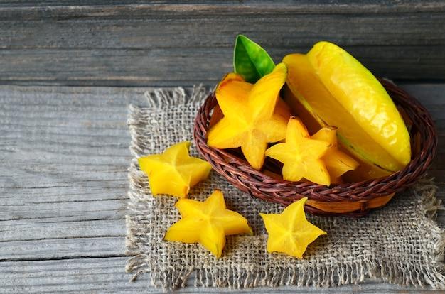 古い木製のテーブルの小さなバスケットに熱帯のエキゾチックなフルーツゴレンシ。starfruitまたはaverrhoaゴレンシの背景。健康食品、ベジタリアンやダイエットのコンセプト。