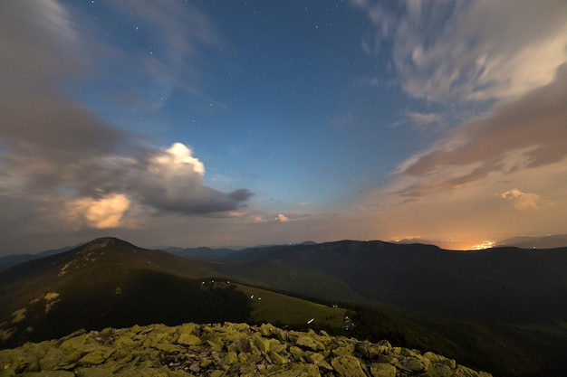 Starry dark blue sky and white clouds at sunset over mountain range.