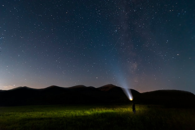 Starry night sky over mountains and man with a flashlight. natural landscape.