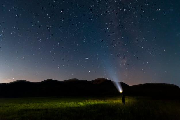 산과 손전등을 가진 남자 위에 별이 빛나는 밤 하늘. 자연 경관.