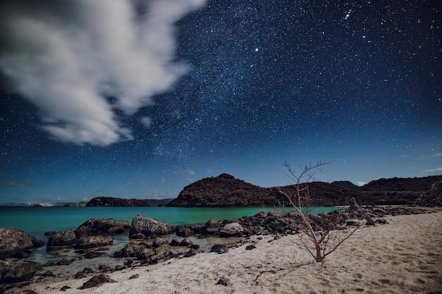 Звездное ночное небо над песчаным пляжем с бирюзовым морем, плайя сантиспак, мексика