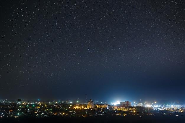 Звездное ночное небо над городом.