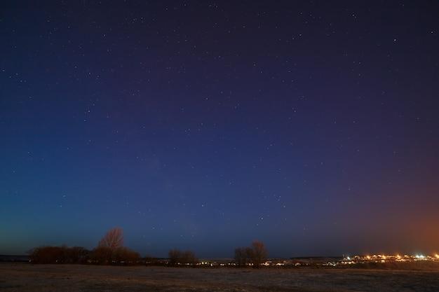 Звездное небо над городской окраиной с уличным освещением