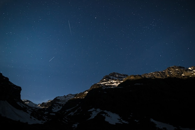 The starry sky on the alps illuminated by moonlight.