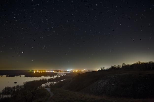 Звездное небо ночью над городом и лесом. пейзаж с длинной выдержкой.
