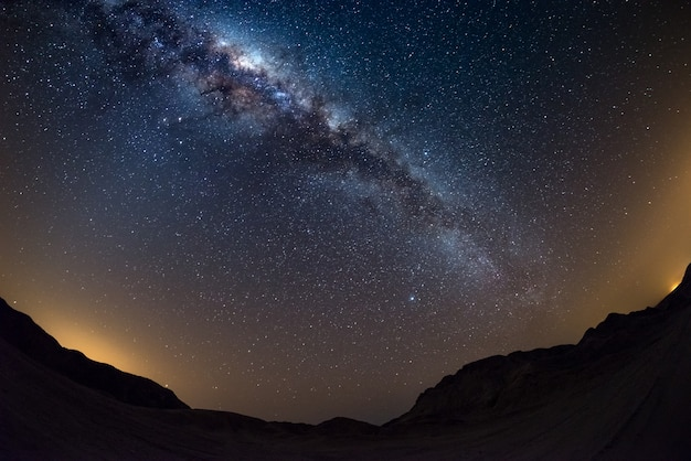 Starry sky and milky way arch, with details of its colorful core, outstandingly bright, captured from the namib desert in namibia.