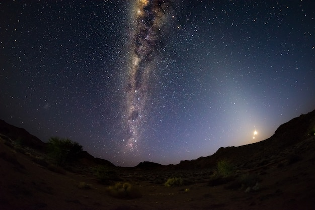 Starry sky and milky way arch with rising moon, captured from the namib desert in namibia, africa.