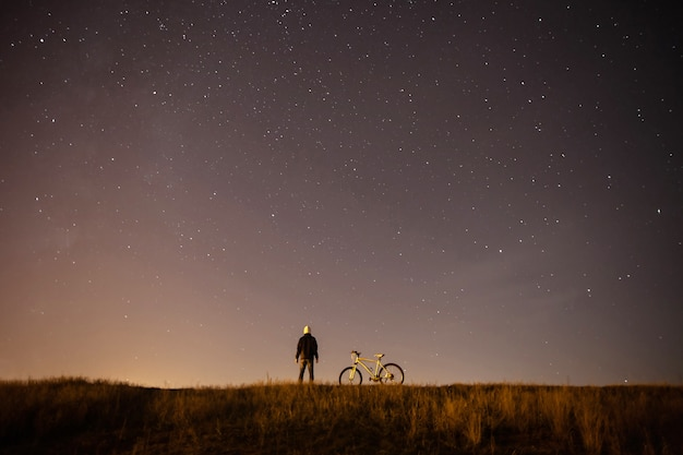 Starry sky, night , astrophotography, the silhouette of a man, a man standing next to a mountain bike on the  of a starry sky, the white bicycle
