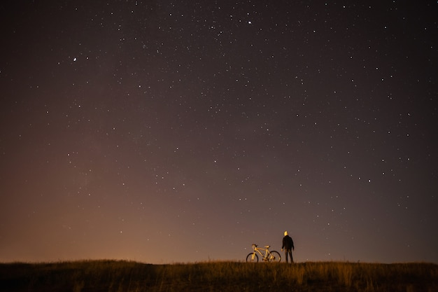 별이 빛나는 하늘, 야간 사진, 천체 사진, 남자의 실루엣, 별이 빛나는 하늘 배경에 산악 자전거 옆에 서있는 사람, 하얀 자전거