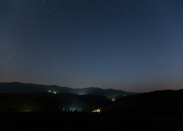 夏の夜に山と山の村の上の星空。
