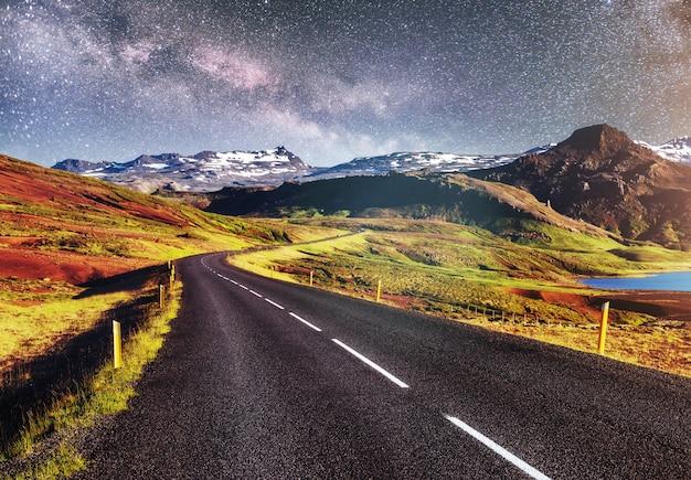 산 위에 별이 빛나는 하늘. 흰색 표시가있는 아스팔트 도로.