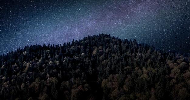 부분적으로 눈 덮인 산 꼭대기에 별이 빛나는 하늘. 그림 같은 밤 풍경.