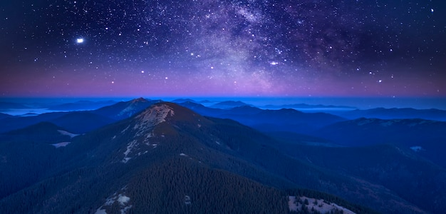 Starry sky over the tops of forested mountains. fog is spreading in the intermountains. wonderful night mountain landscape.